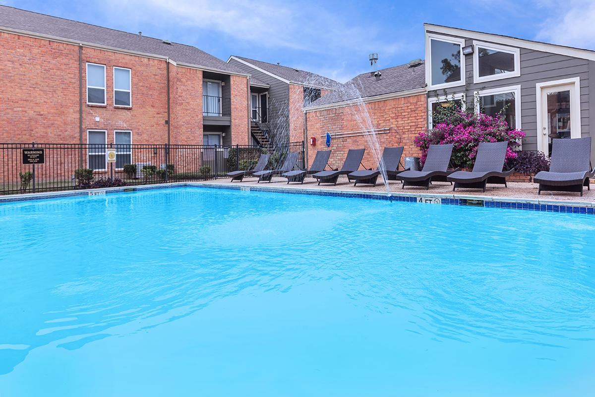 a large brick building with a pool of water