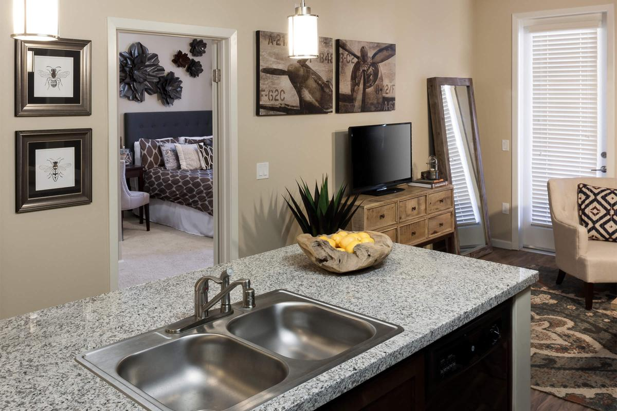 Close up of kitchen sink with bedroom and living room in background