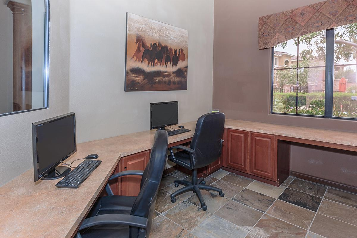 a room with a desk and chair in front of a window