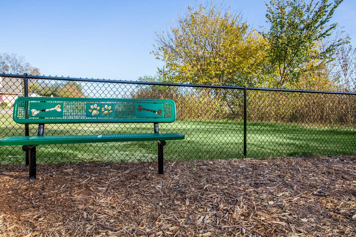 a close up of a green park bench sitting in front of a fence