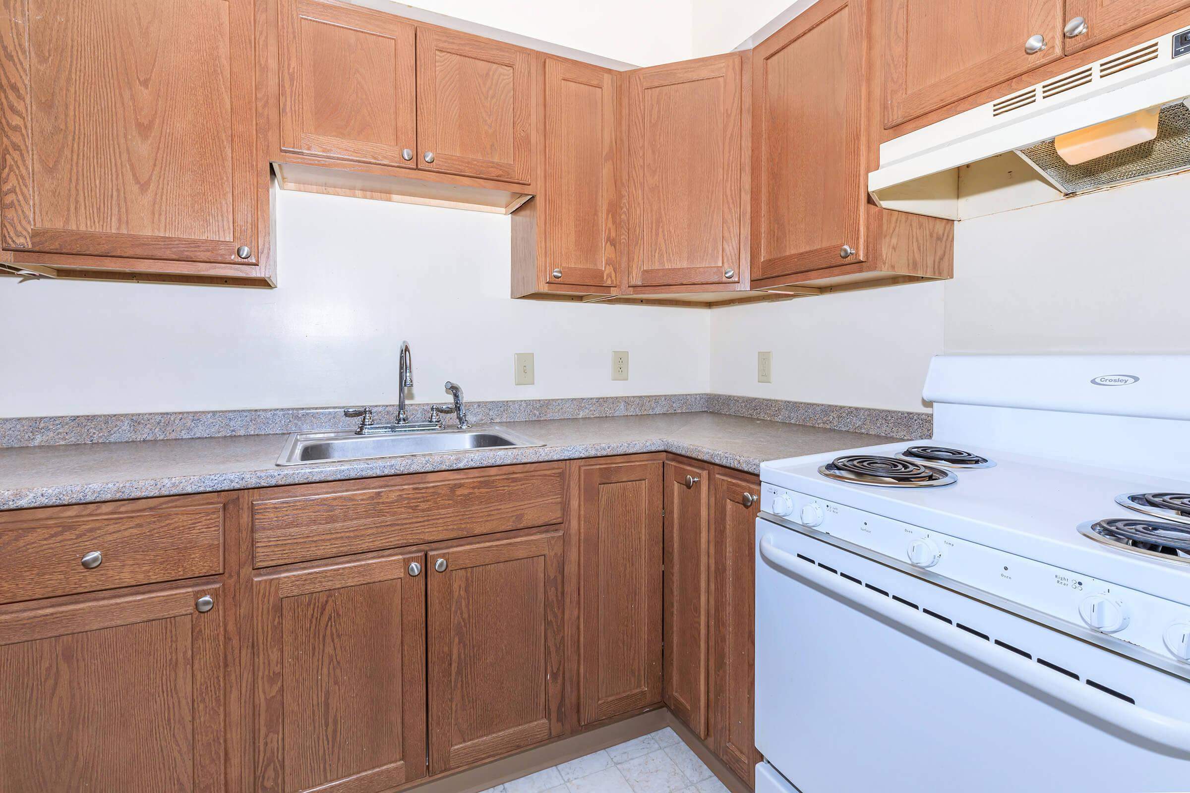 a kitchen with wooden cabinets