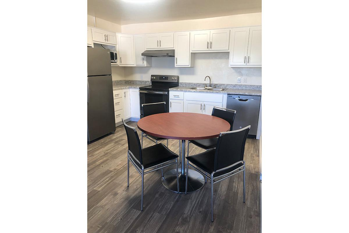 a kitchen with wooden cabinets and a black chair