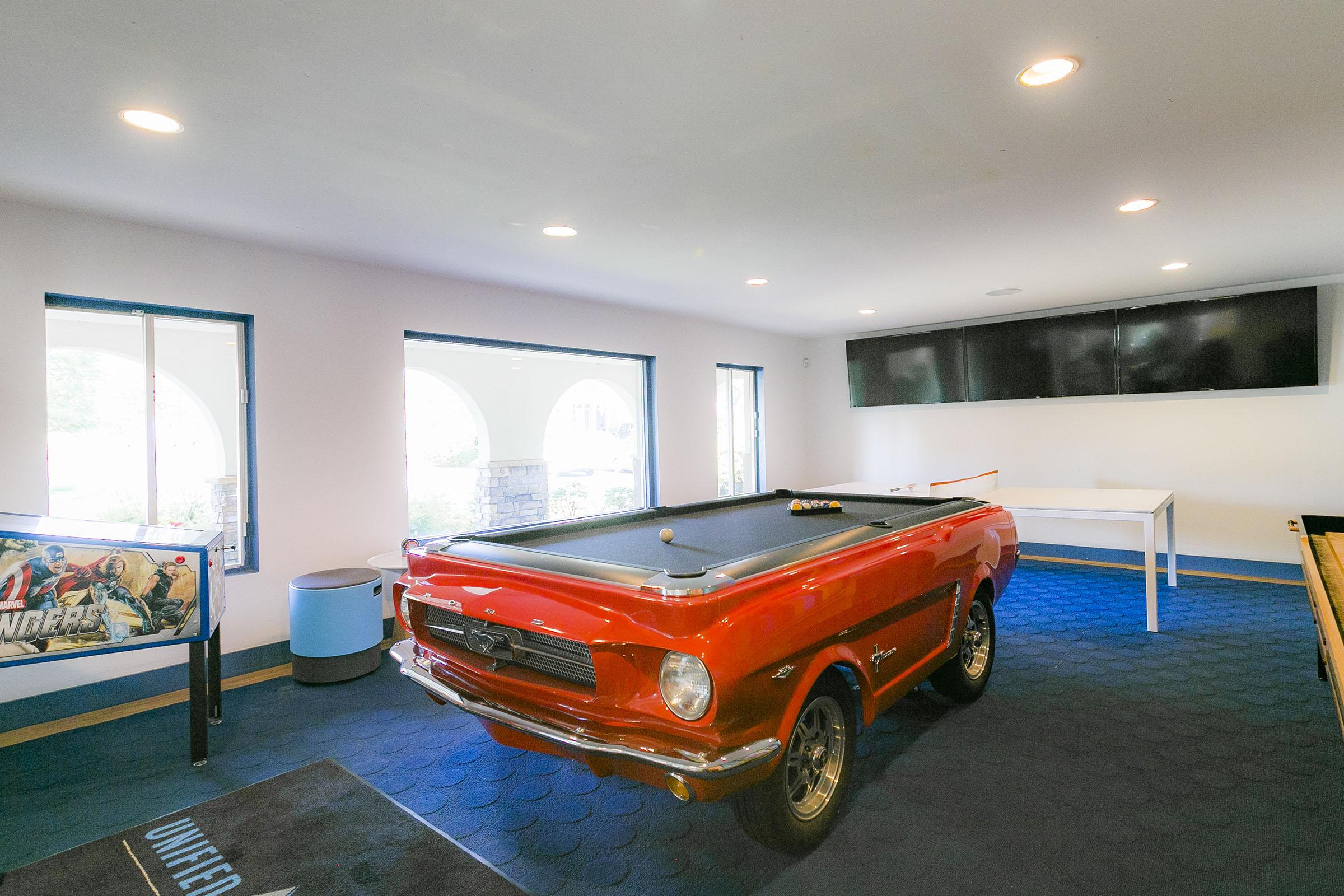 a room filled with furniture and a red car