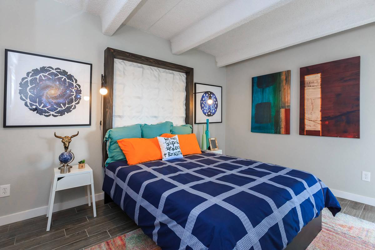 a bedroom with a bed and a painting on the wall