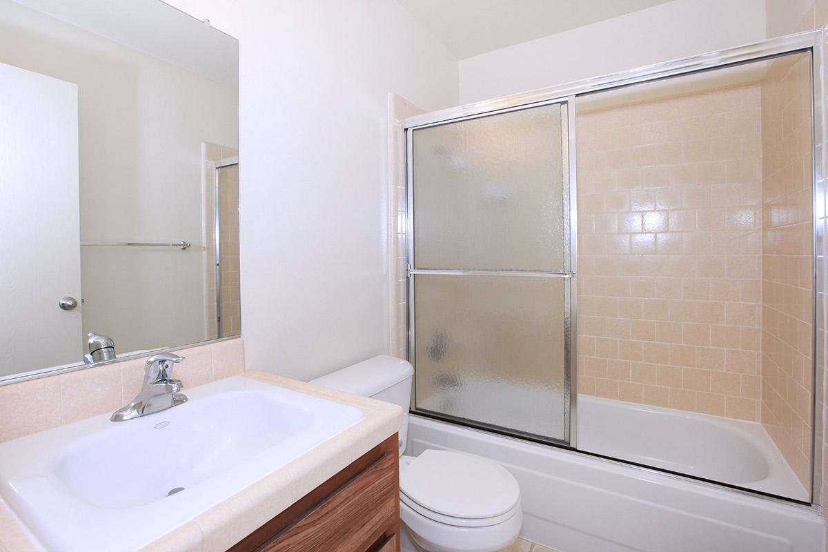 a white sink sitting next to a glass shower door