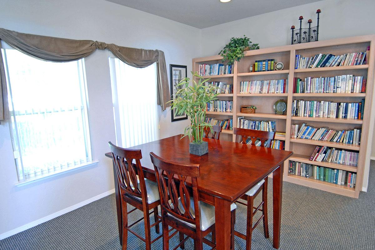 a dining room table and chairs in a library