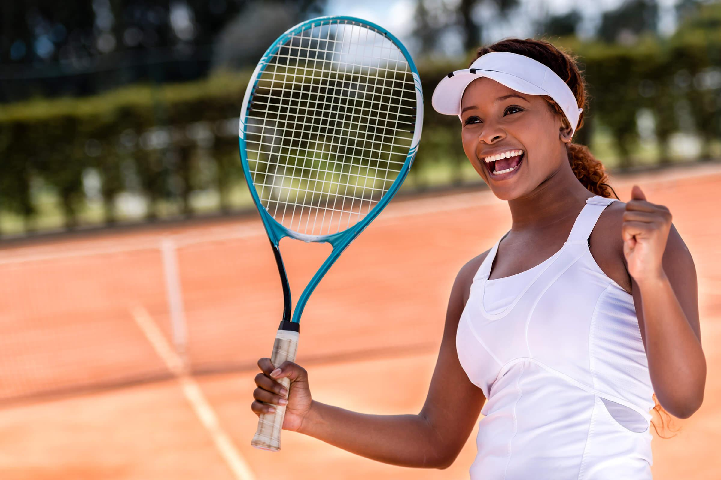 a woman is smiling while holding a racket on a court