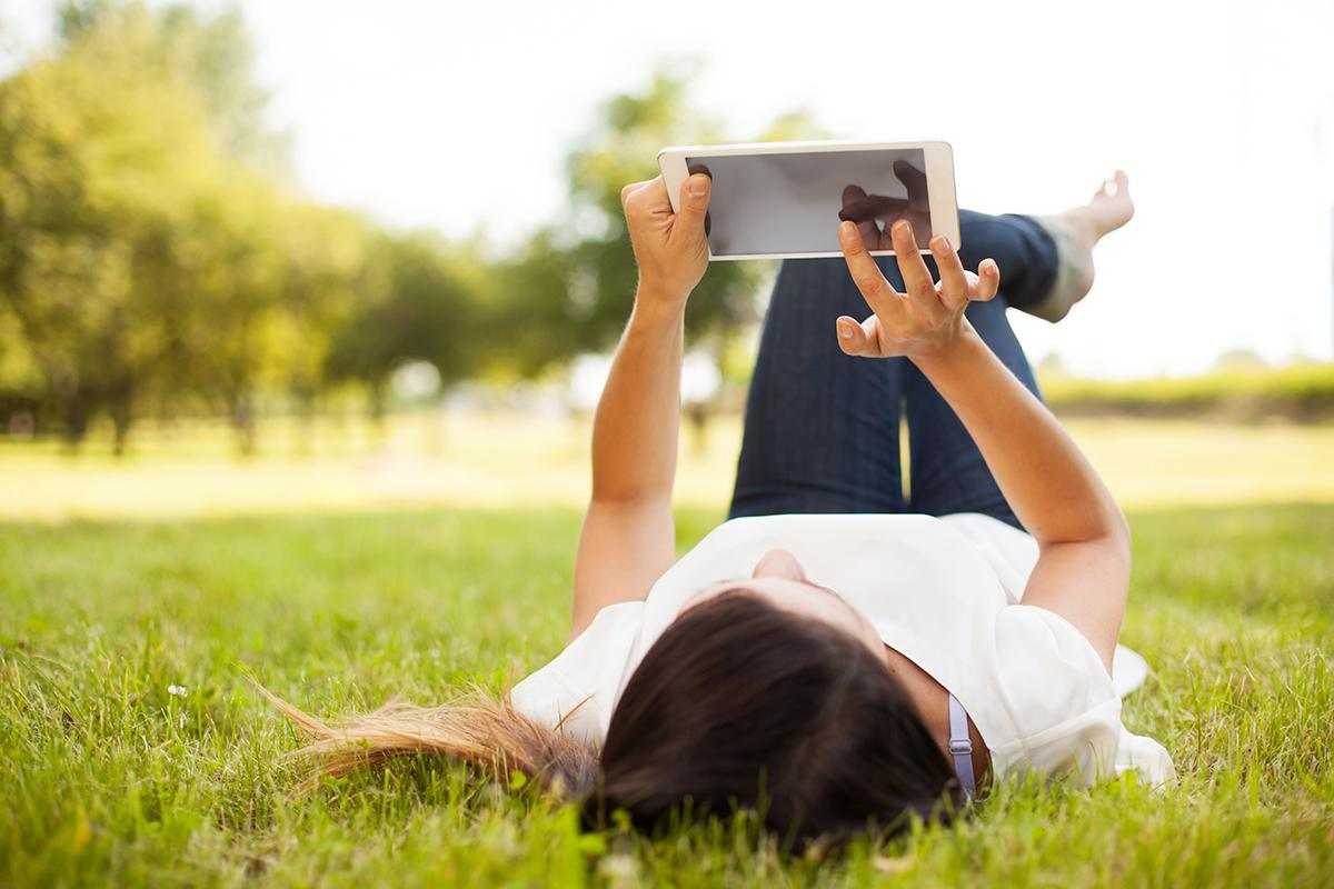 Women Laying In The Grass With Her Tablet