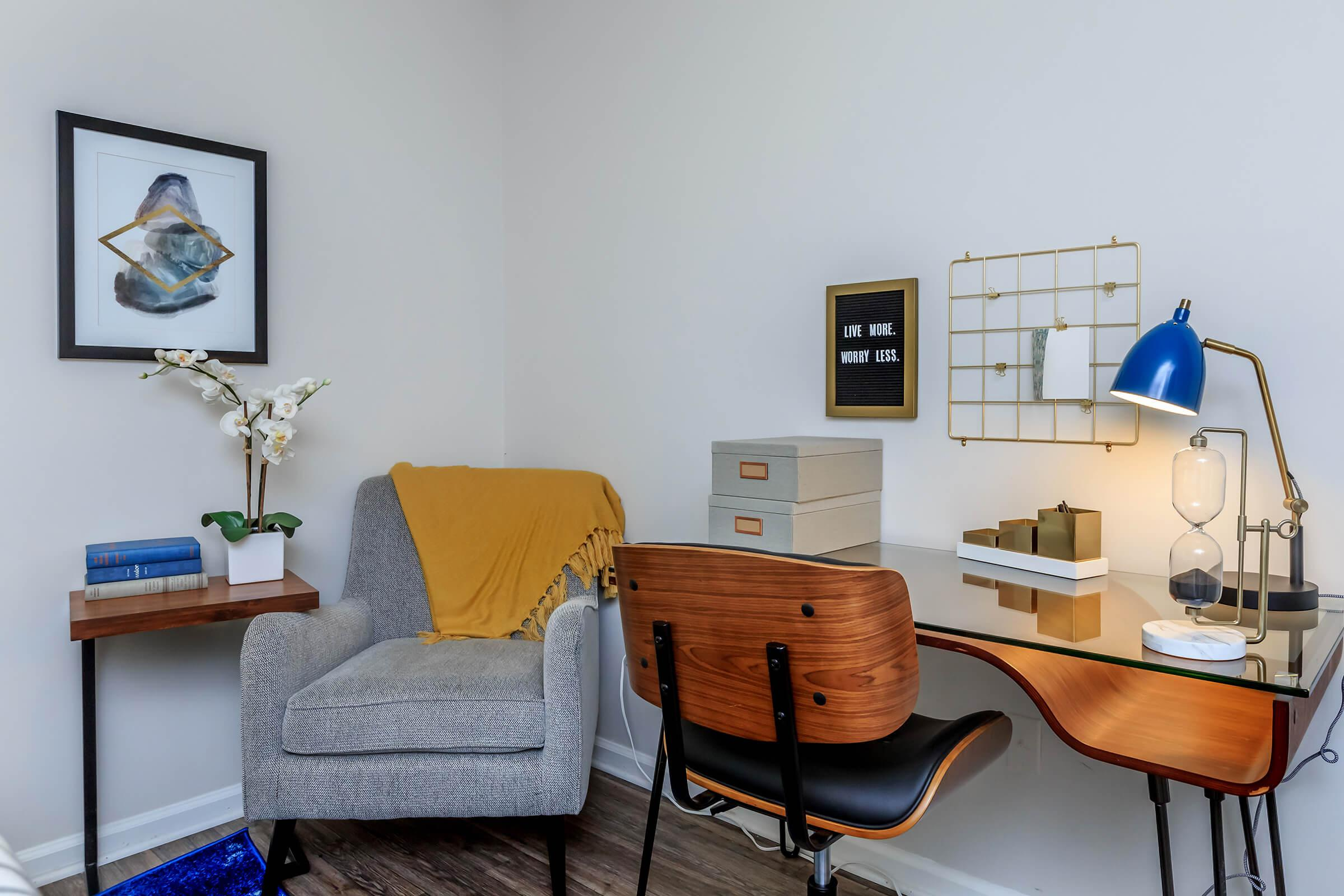 a living room with a desk and chair