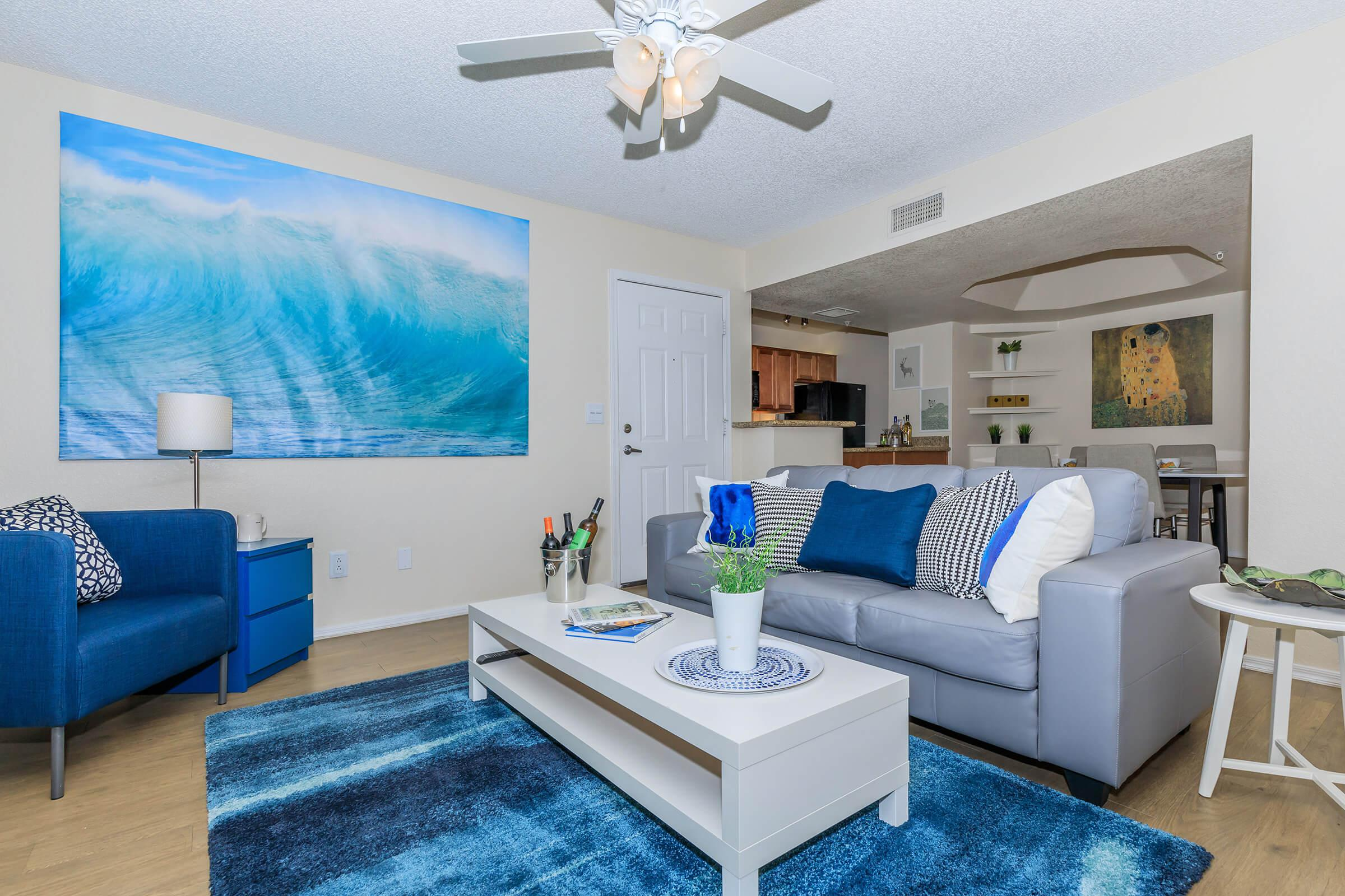 a living room with blue furniture and a flat screen tv