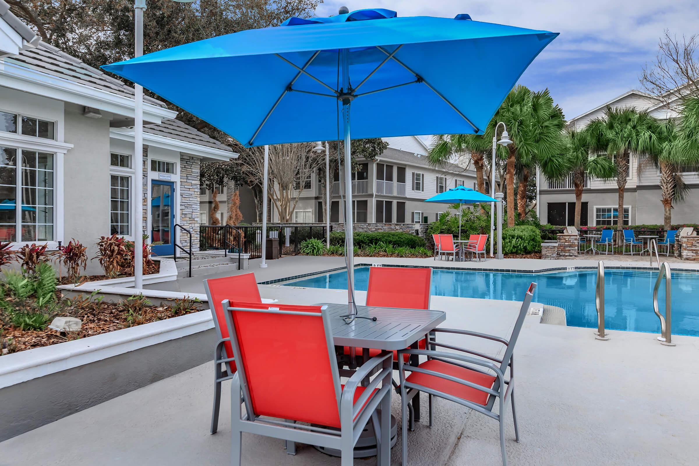 a blue umbrella sitting on a chair in front of a house