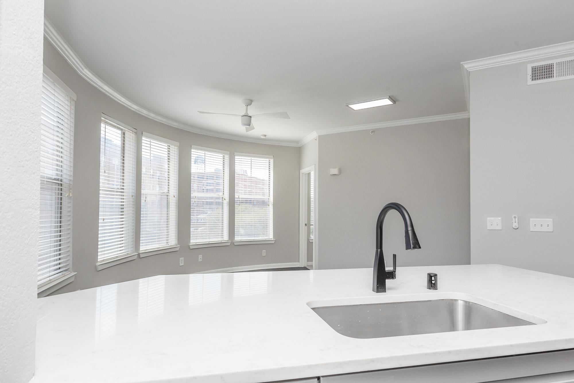 a white sink under a mirror next to a window