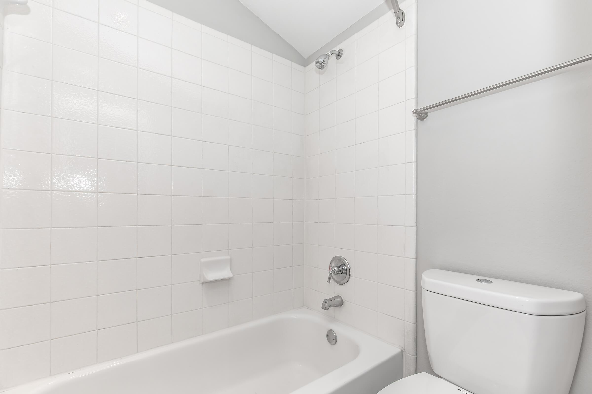 a white sink sitting next to a tiled wall