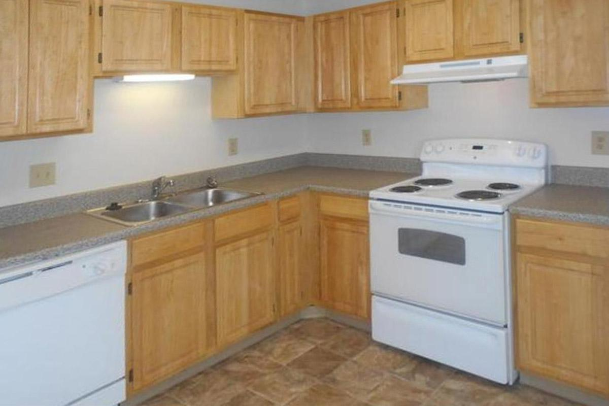 a kitchen with wooden cabinets and a white stove top oven