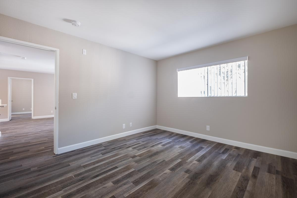 Bedroom with hardwood floors and vertical blinds