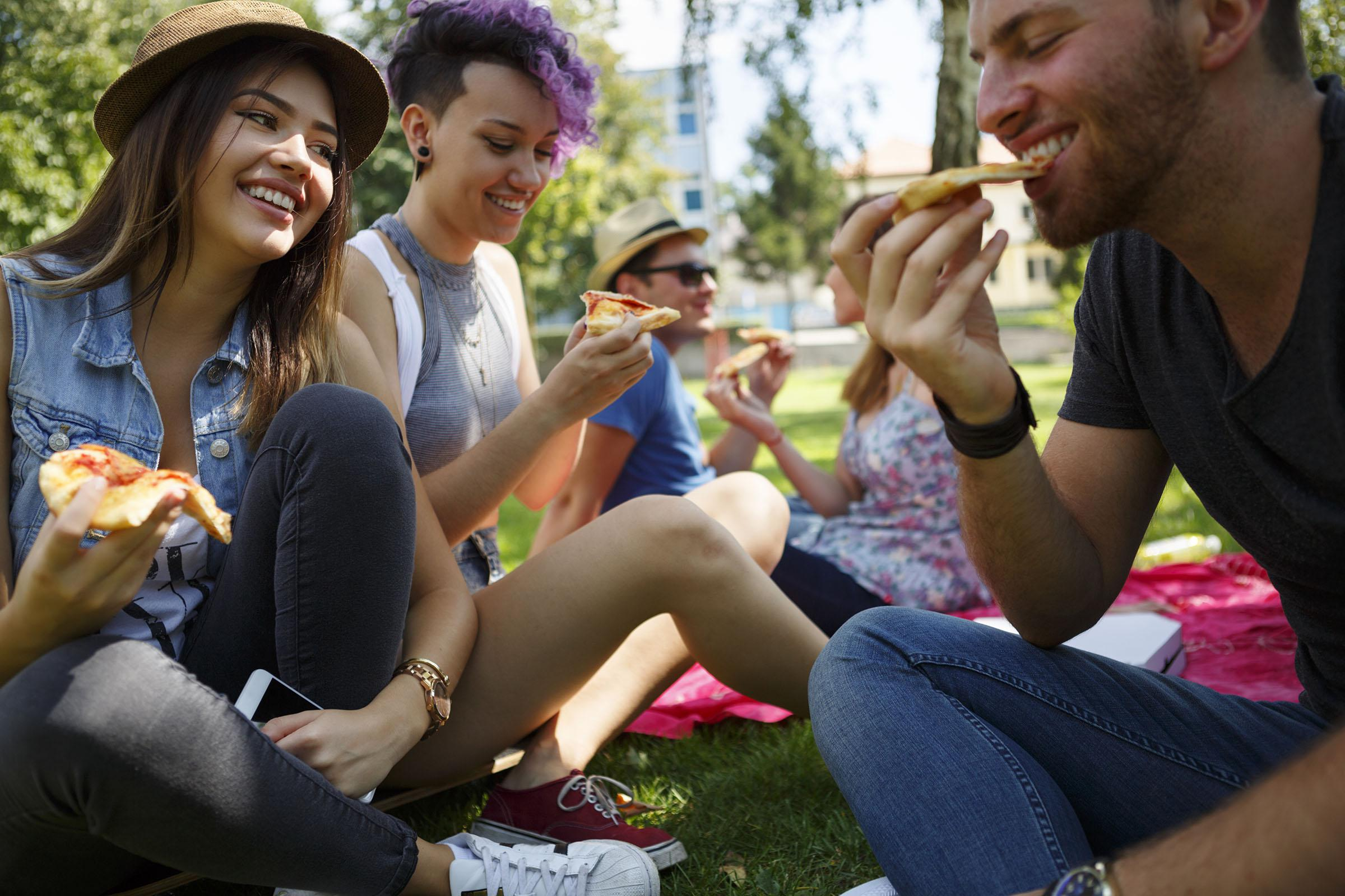 a group of people eating hot dogs