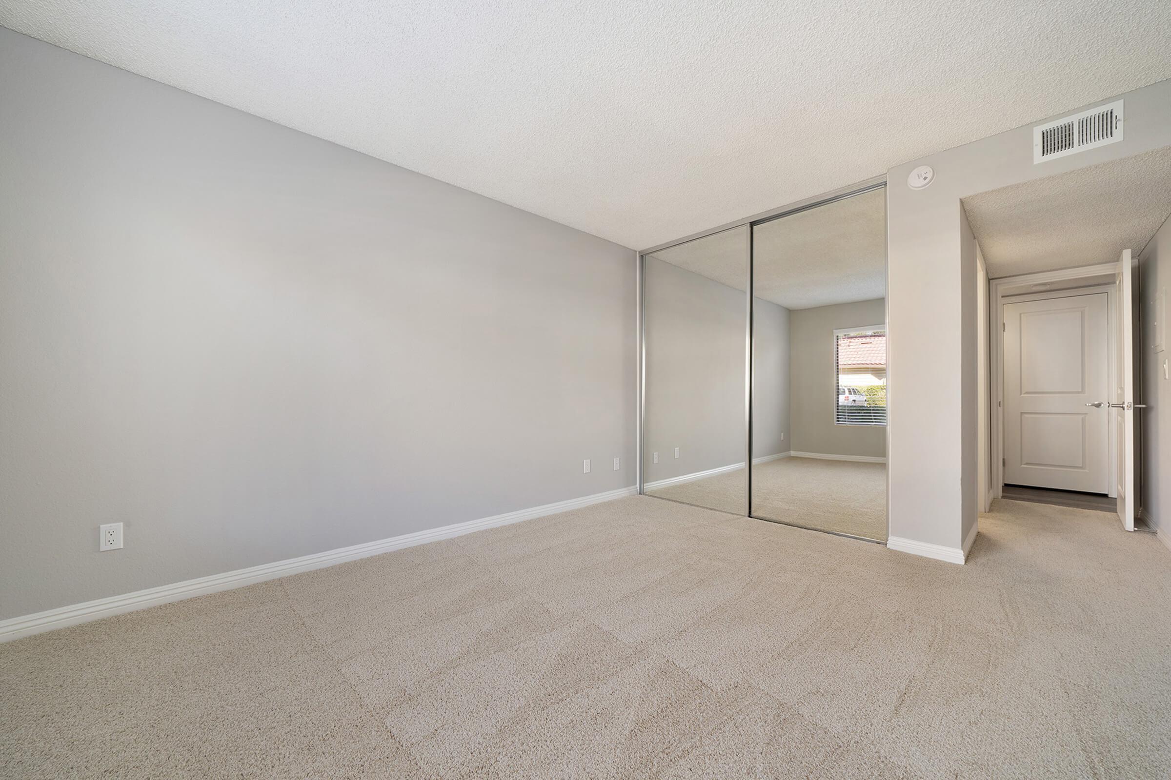Bedroom with sliding mirror glass closet doors