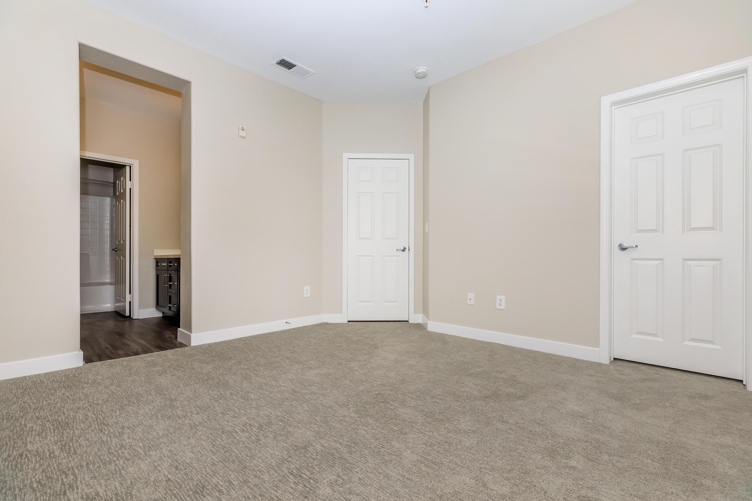 Bedroom with open bathroom door