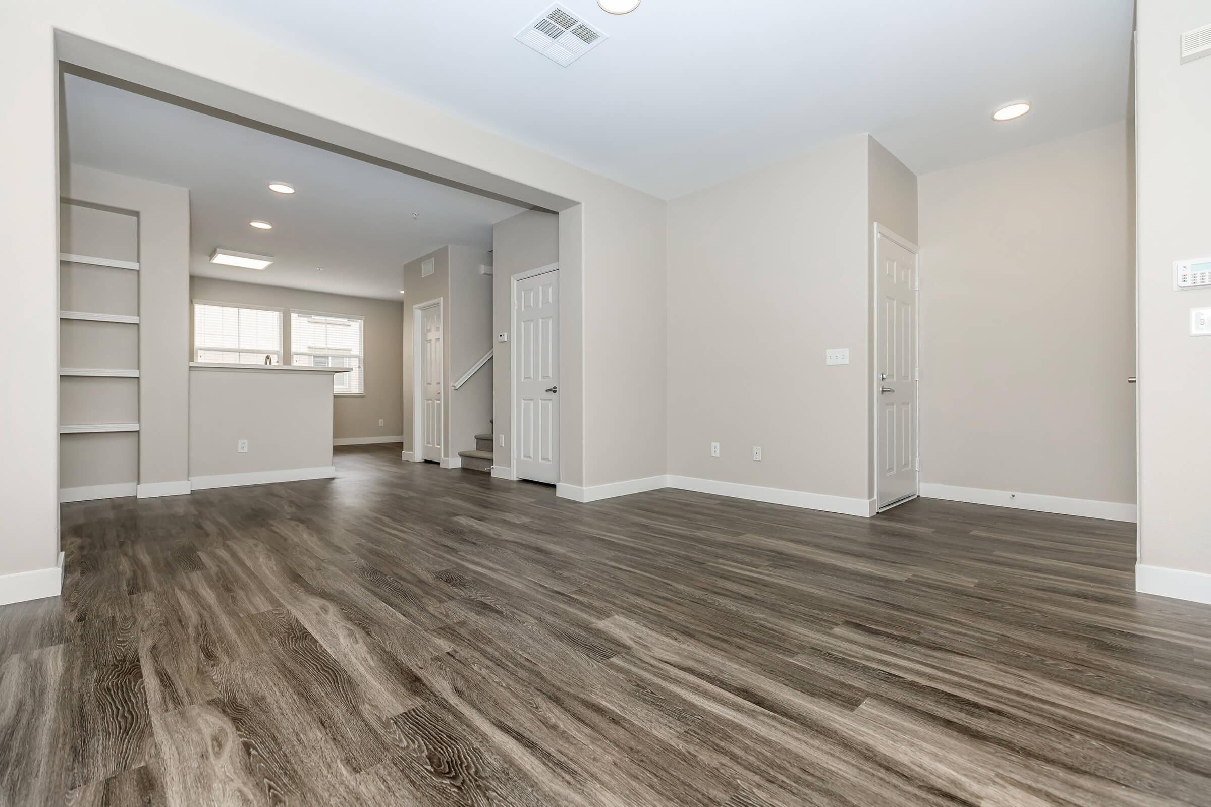 Unfurnished living room and dining room with wooden floors