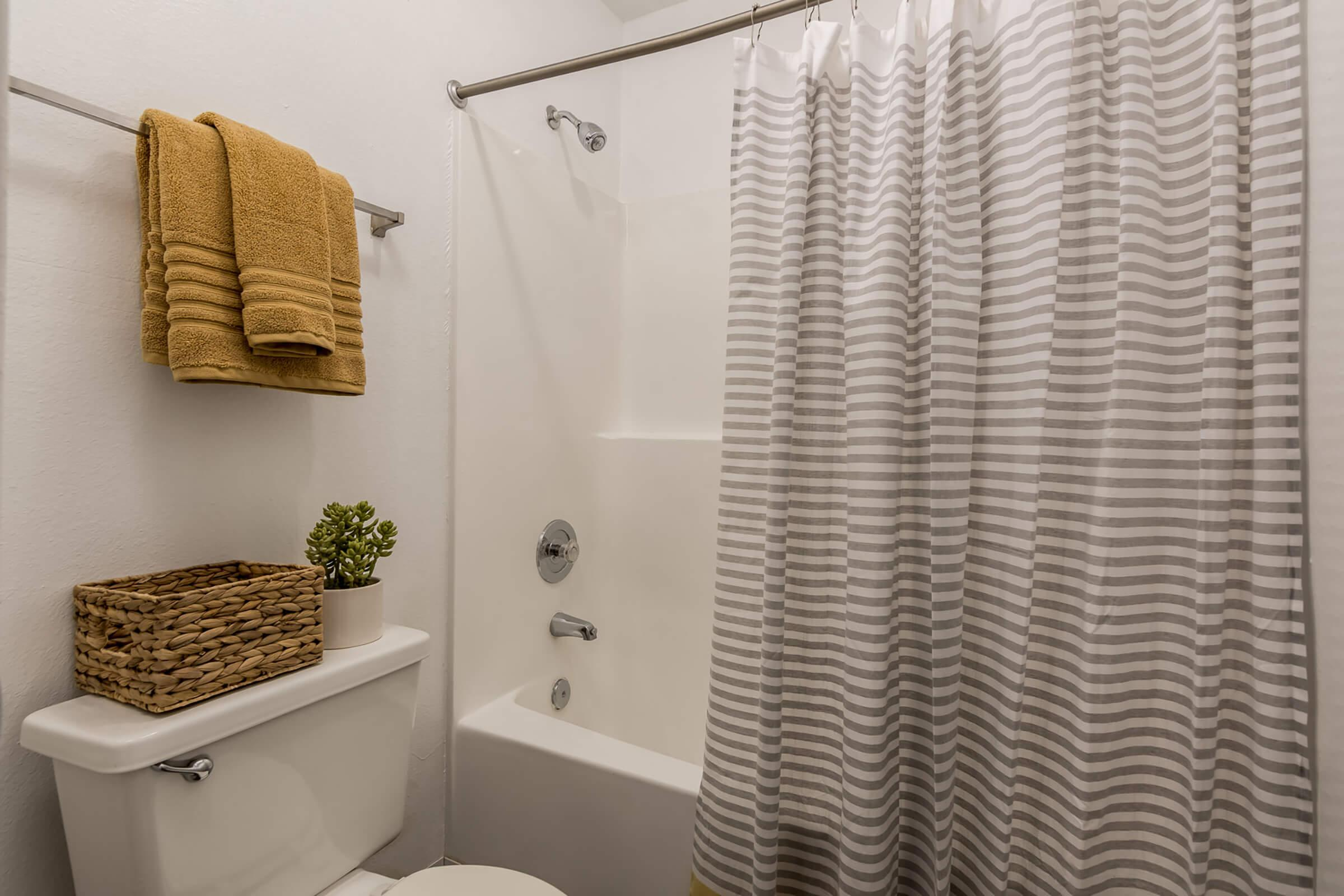a room with a sink mirror and shower curtain