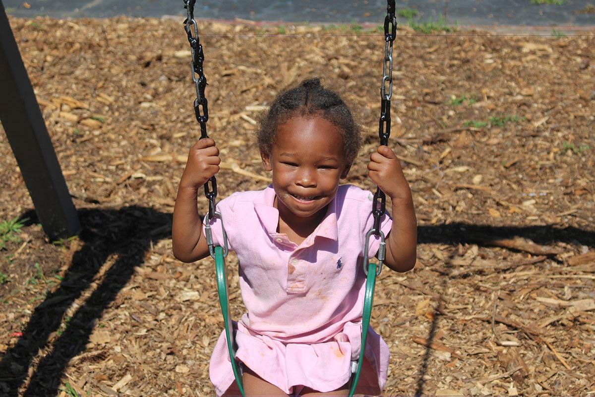 a little girl in a swing