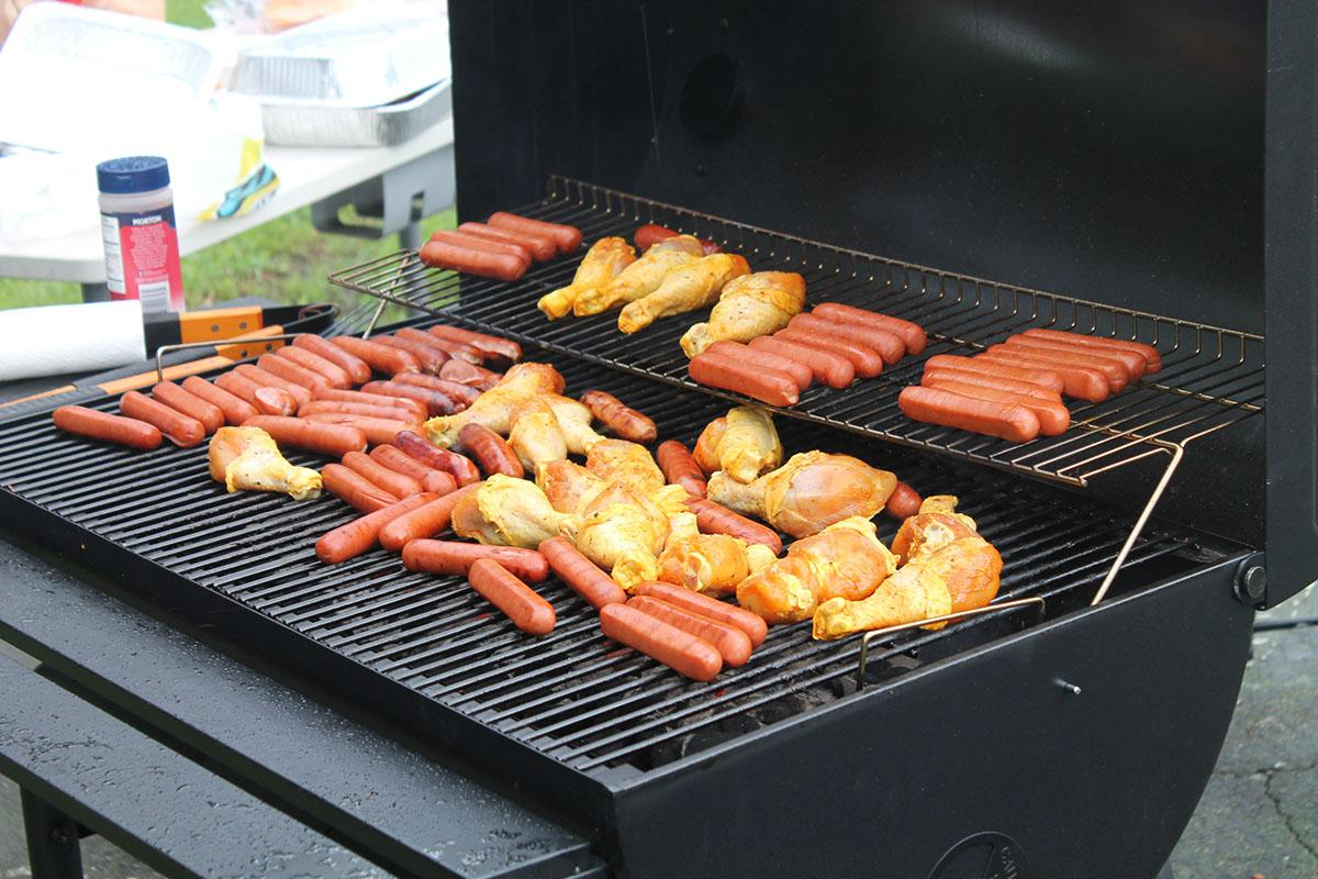 a bunch of hot dogs cooking on a grill