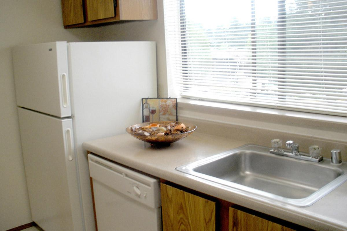 a kitchen with a stove a sink and a window
