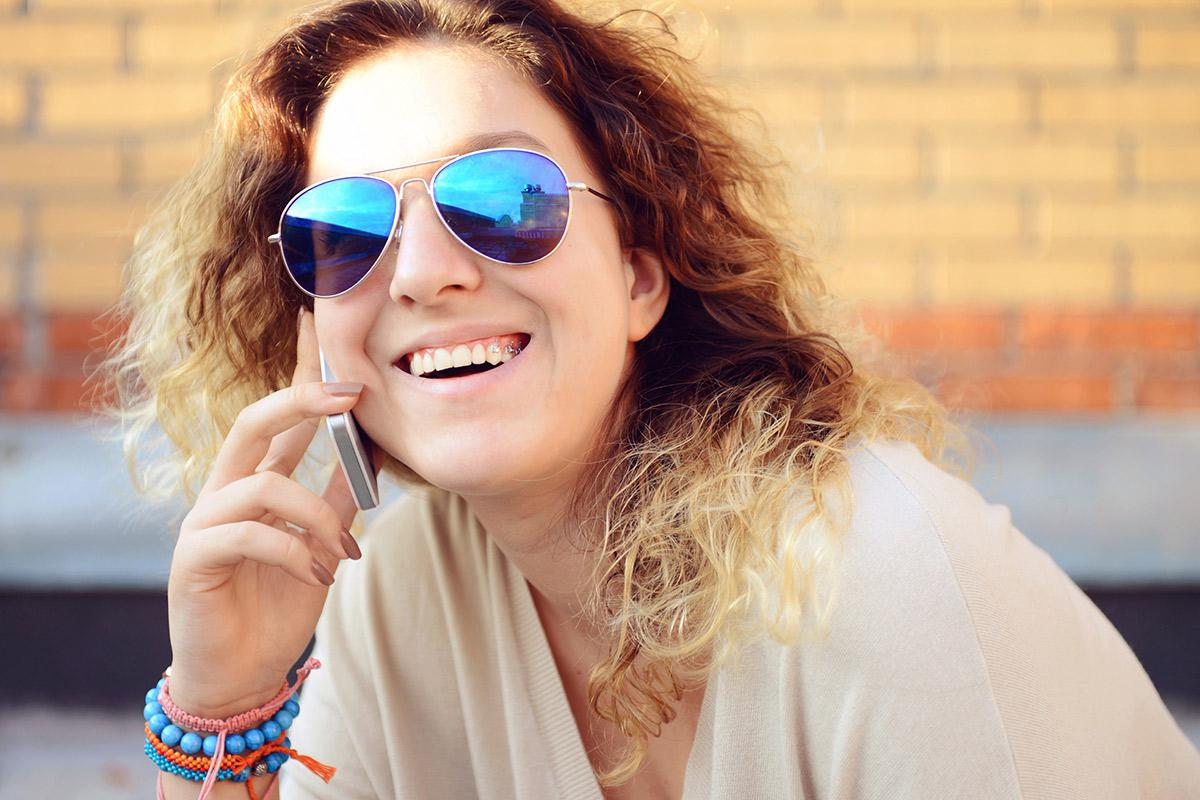 a woman wearing sunglasses talking on a cell phone
