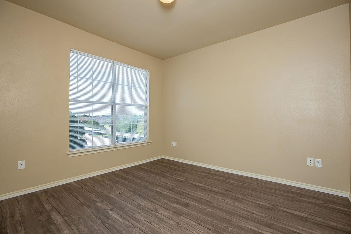a room with wood floors and a large window