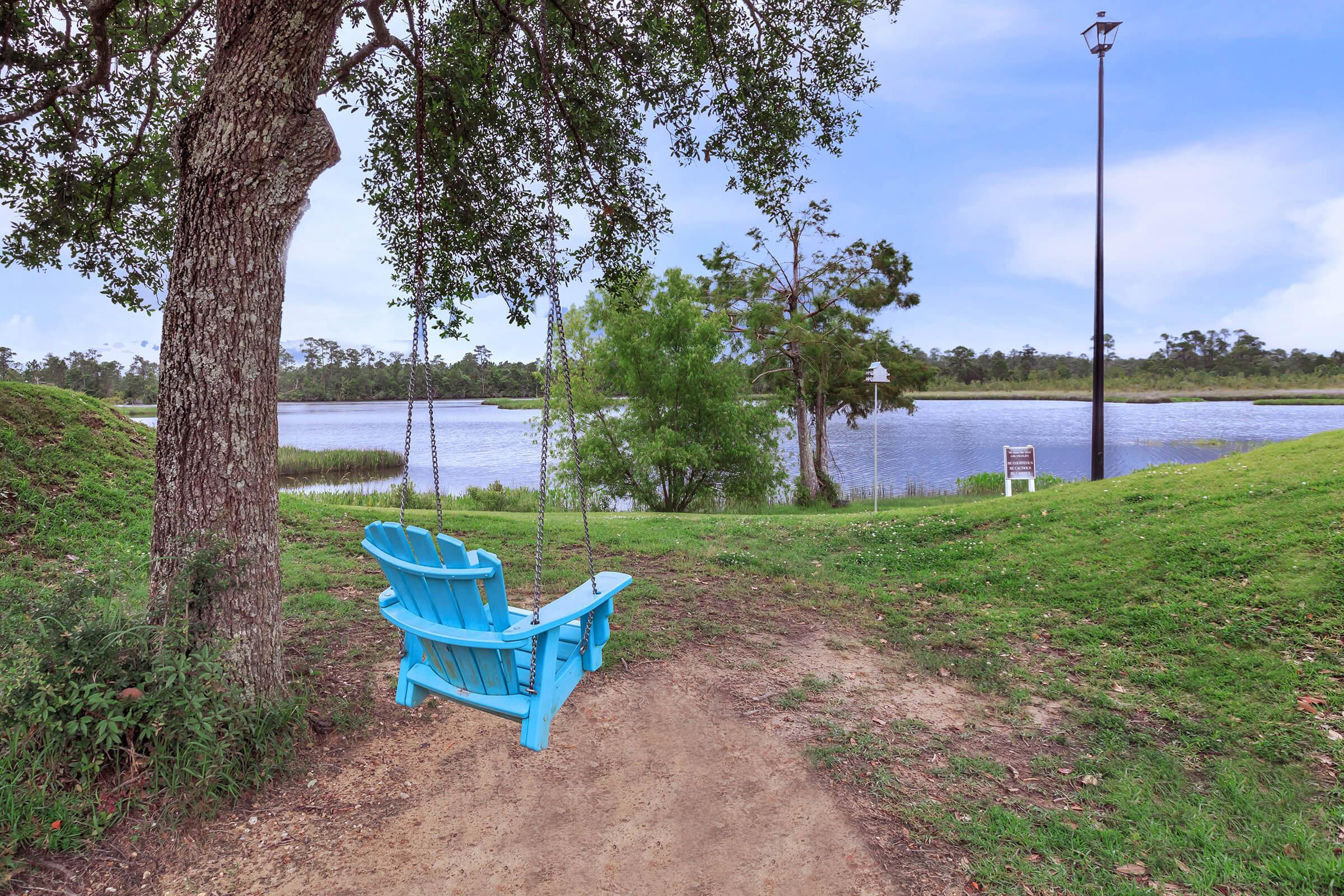 a blue bench in front of a body of water