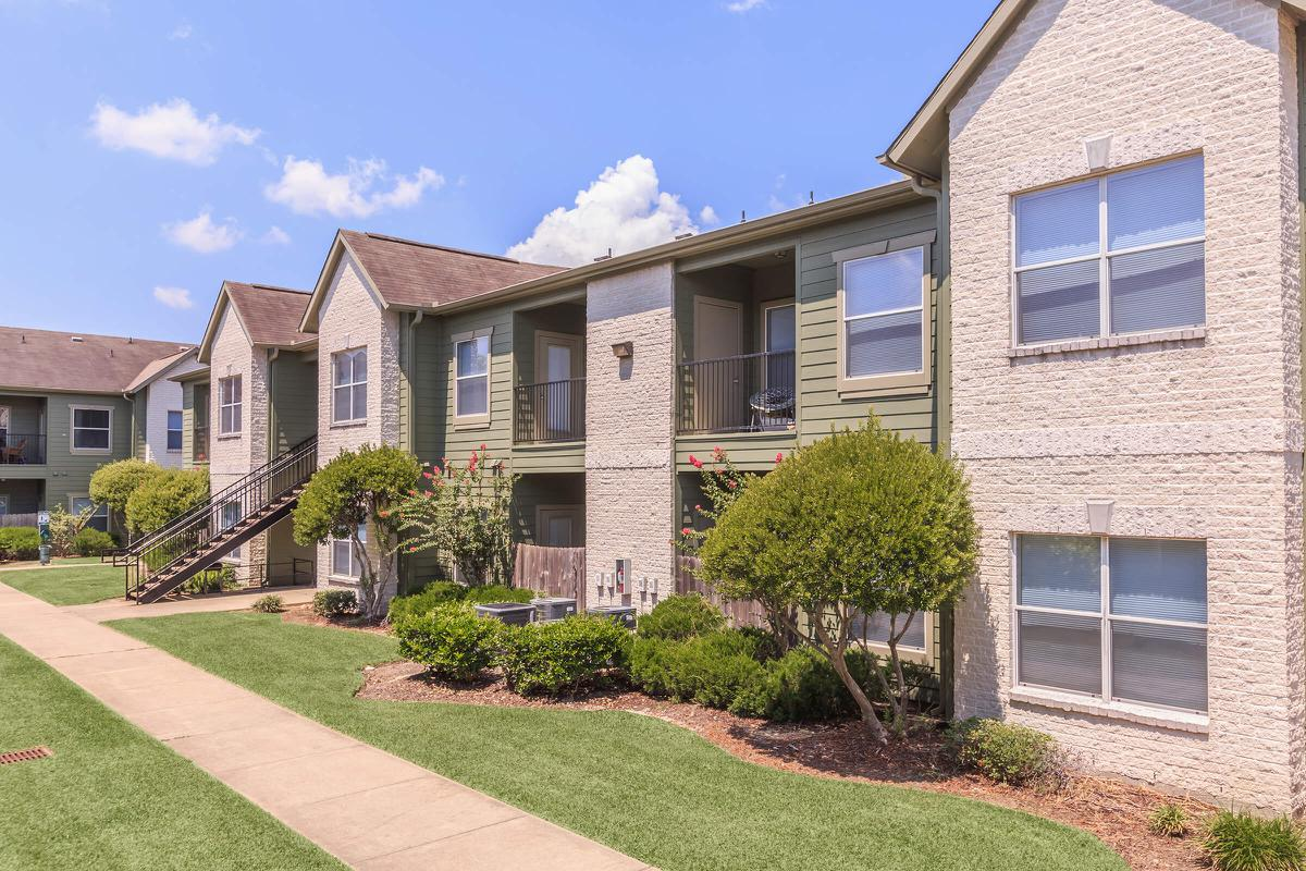 Exterior view of residential buildings with beautiful landscaped grounds at The Avenue apartments