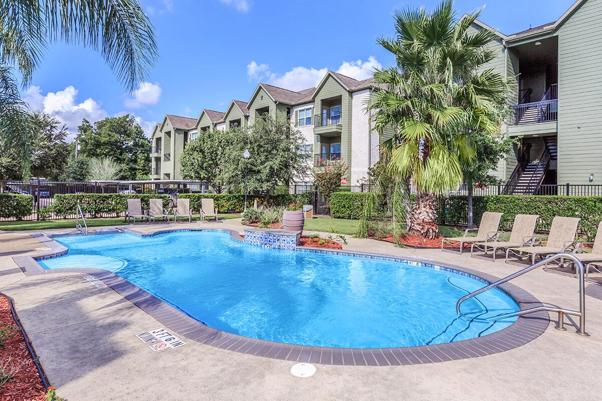 Shimmering outdoor swimming pool with lounge chairs at The Avenue apartments