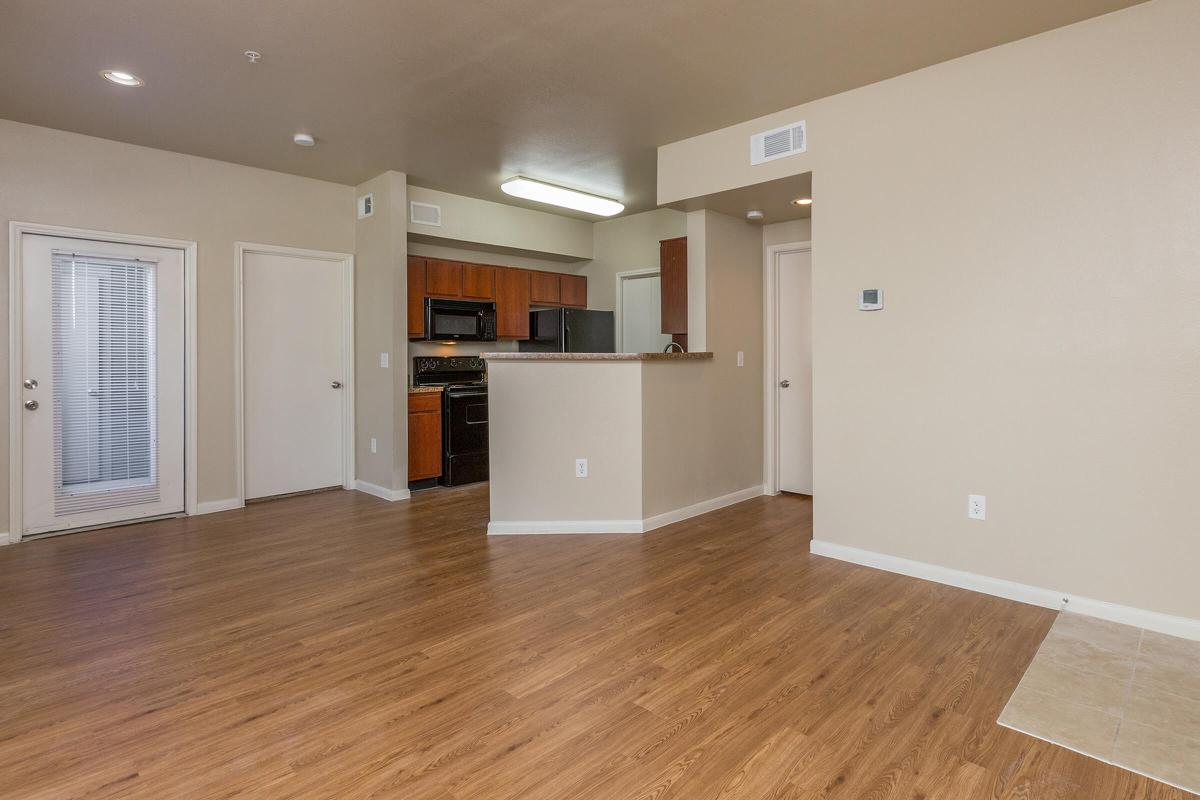 Large apartment living room with 9-foot ceilings and view of kitchen
