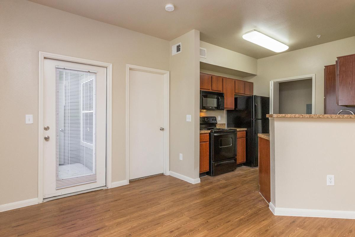 Living room with door to private balcony/patio and view of kitchen