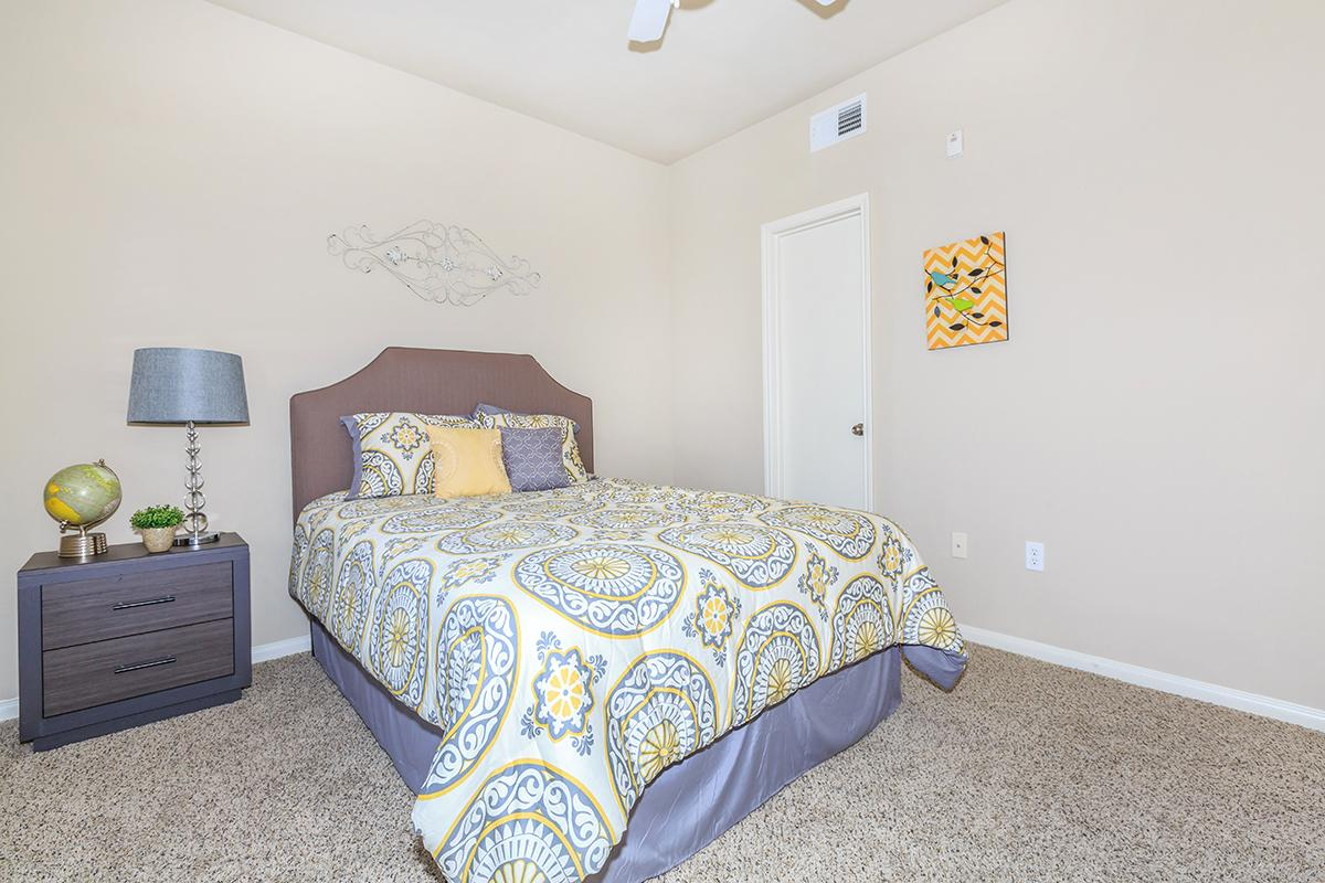 Bedroom with double bed, nightstand, and tan plush carpeting