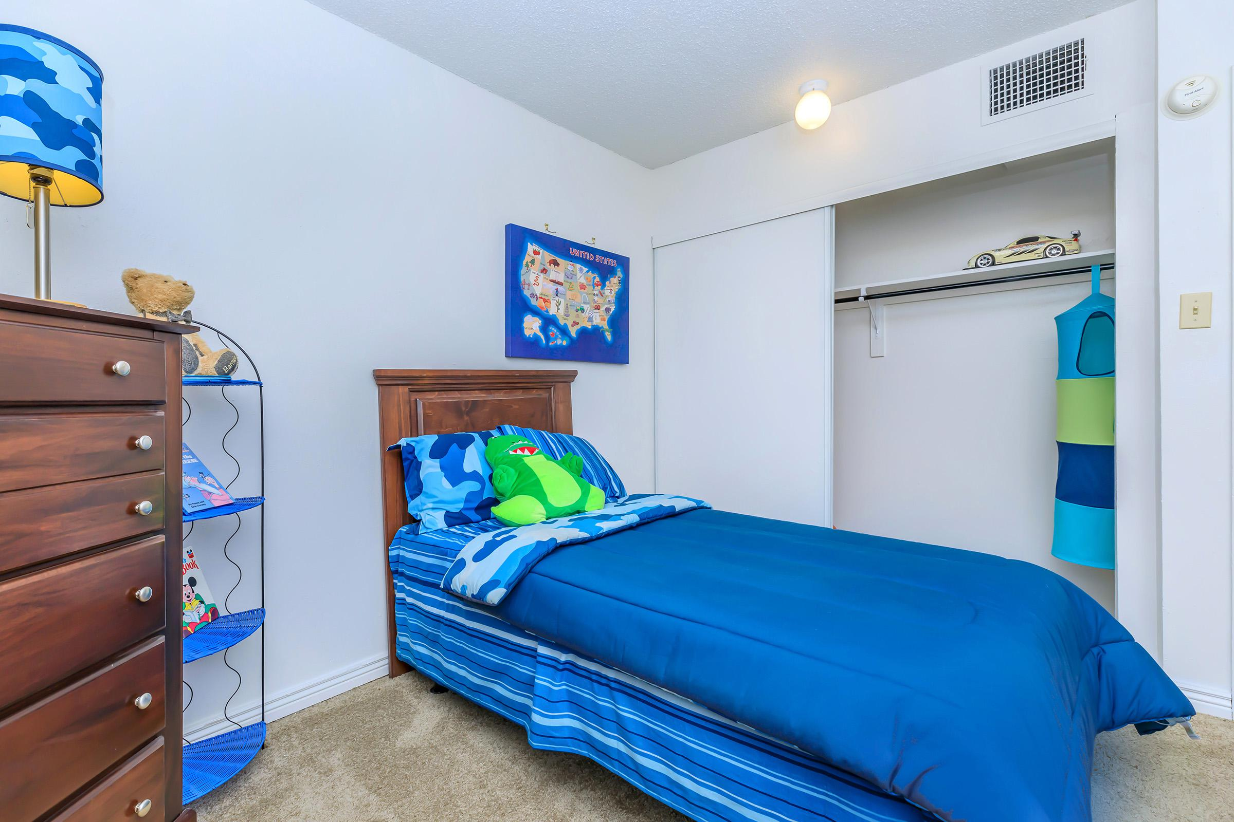 a bedroom with a bed and a blue suitcase