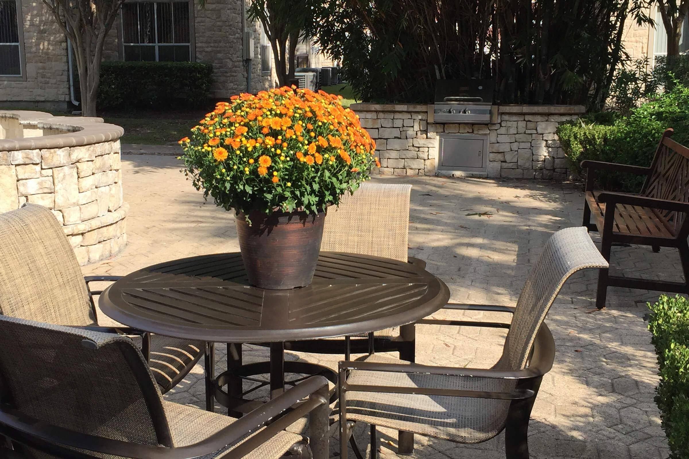 a vase of flowers sitting on a park bench