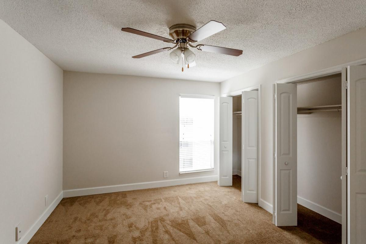 Comfortable bedroom with ceiling fan at Longwood at Southern Hills