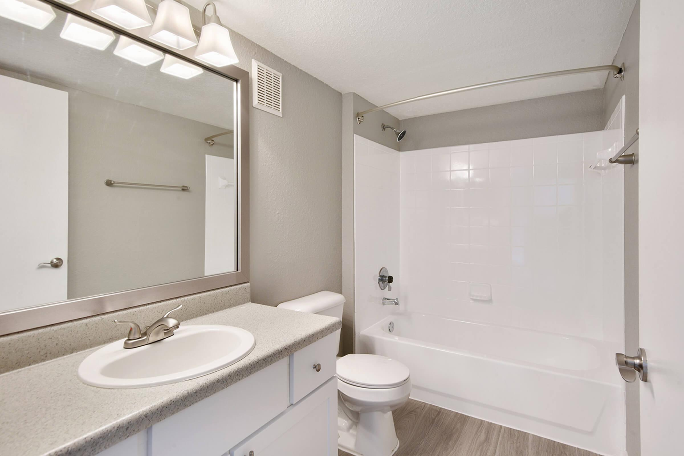 a white sink sitting under a mirror next to a shower