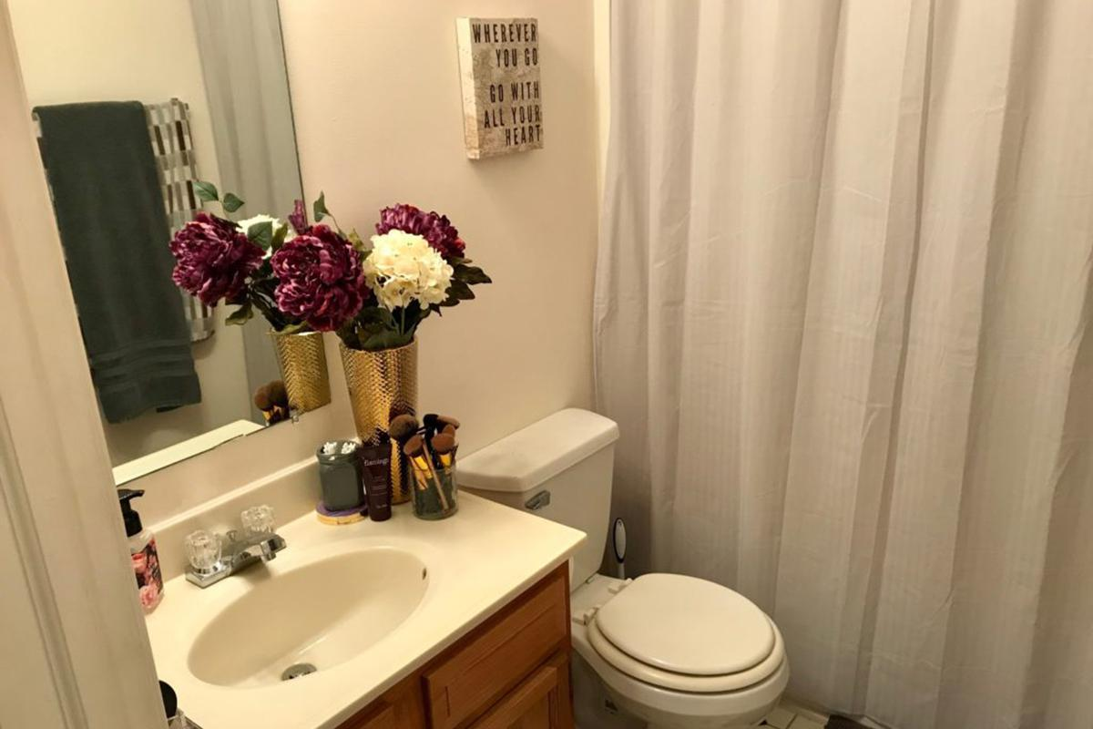a white sink sitting next to a shower curtain