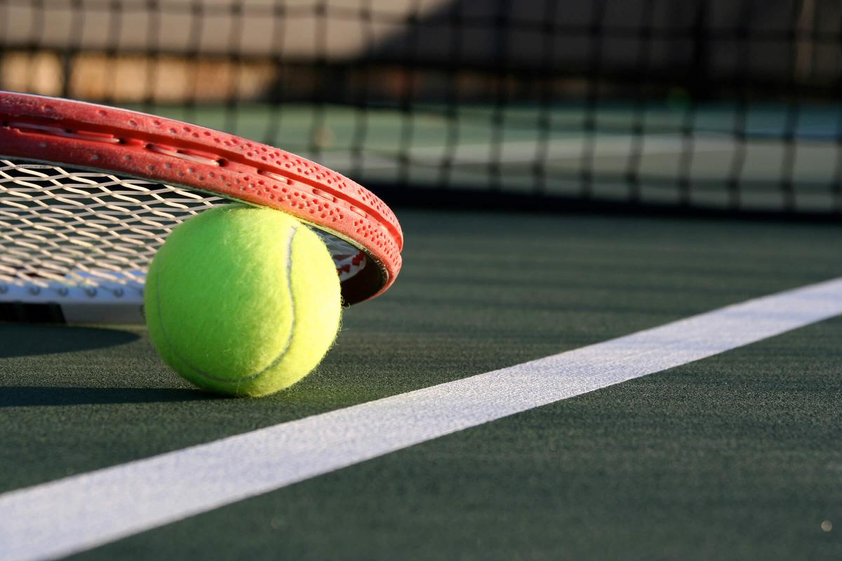 a green ball on a court with a racket
