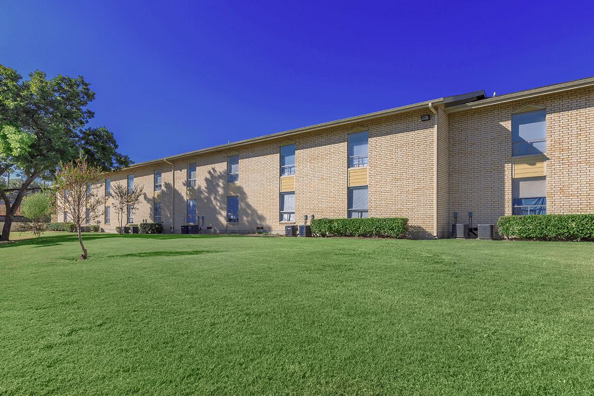 a large brick building with a grassy field with Arlington Court in the background