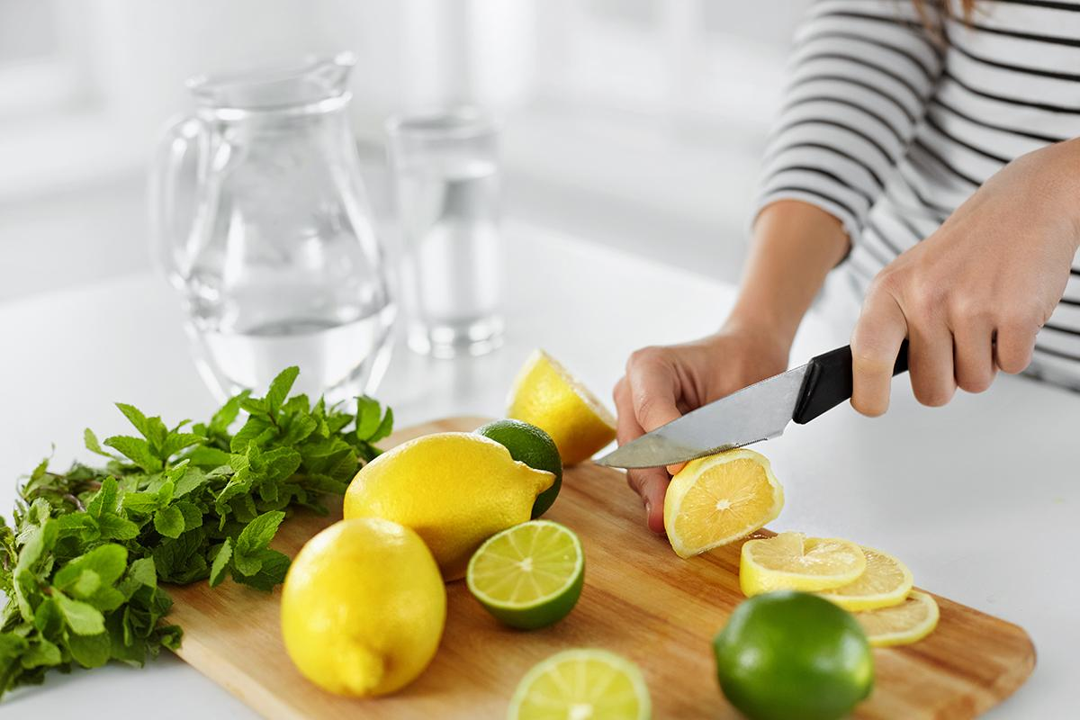 a person with a knife on a cutting board with a cake