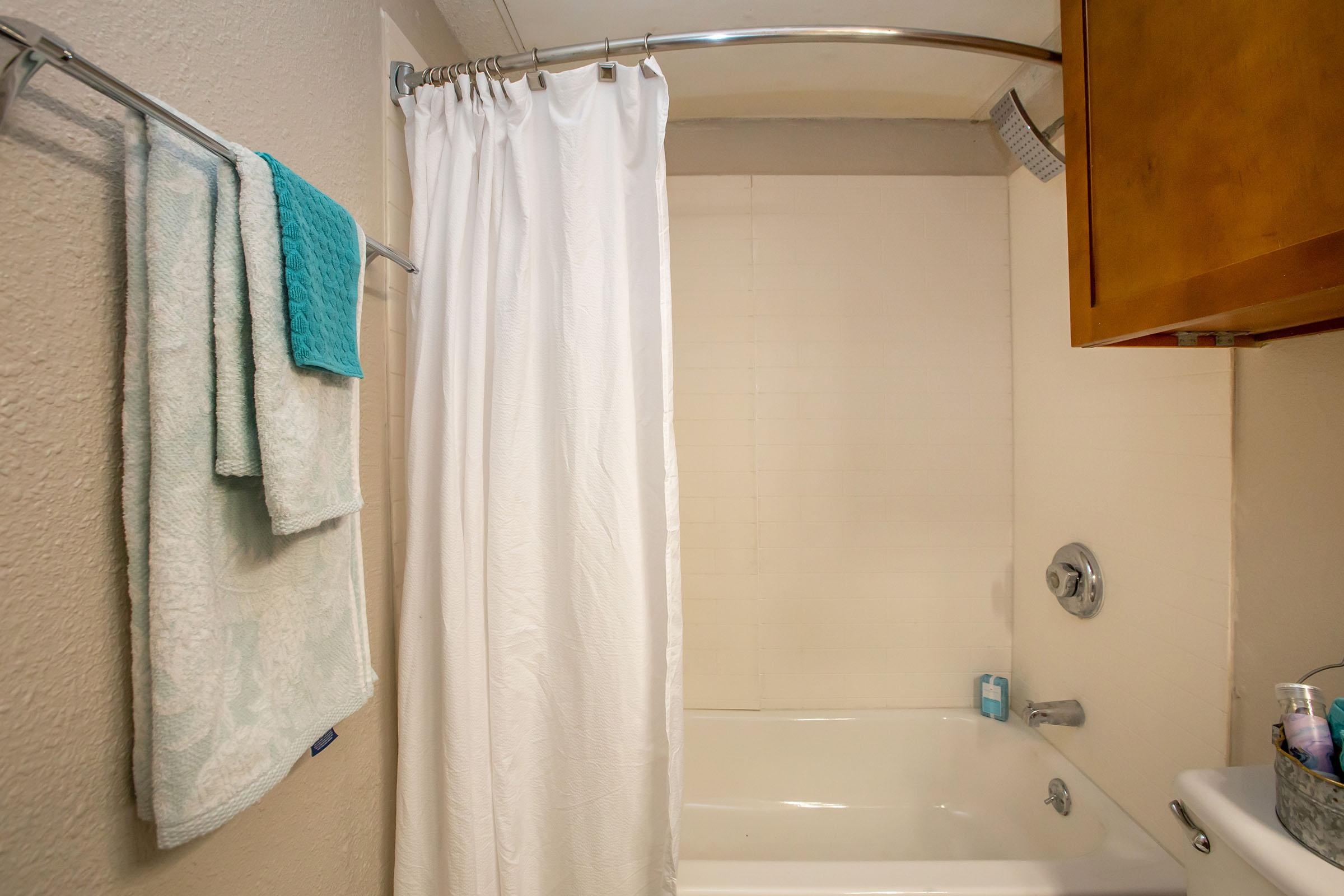 a shower curtain with a towel hanging on the wall